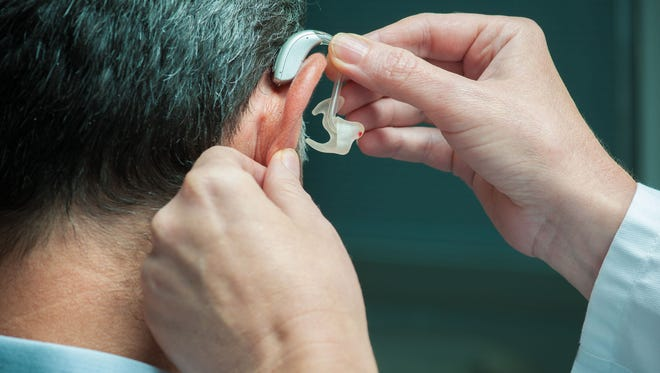 Doctor inserting hearing aid in senior's ear.