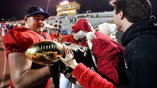 Brentwood Academy's Airin Spell (58) holds the team's trophy after their Division II-AAA state championship victory against MBA at Tucker Stadium in Cookeville, Tenn., Saturday, Dec. 2, 2017.
