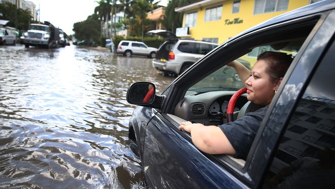 Sandy Garcia sits in her vehicle that was stuck in a flooded street on Sept. 30, 2015, in Fort Lauderdale.