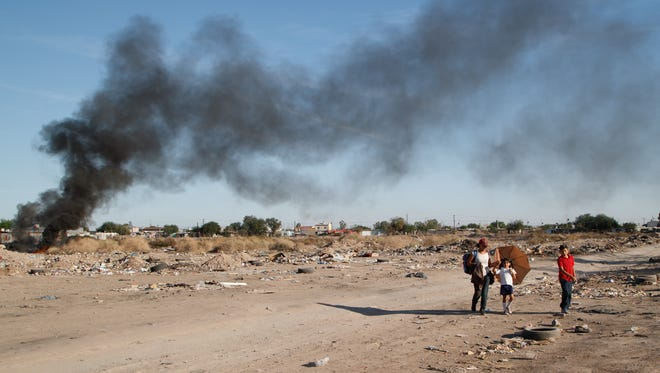A woman walks two children through an empty lot where trash is burning, Mexicali, Mexico, Nov. 16, 2017.