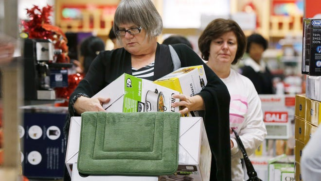 A shopper struggles with boxes as she loads a cart in an aisle at a Kohl's department store in Sherwood, Ark., Thanksgiving evening Thursday, Nov. 27, 2014.