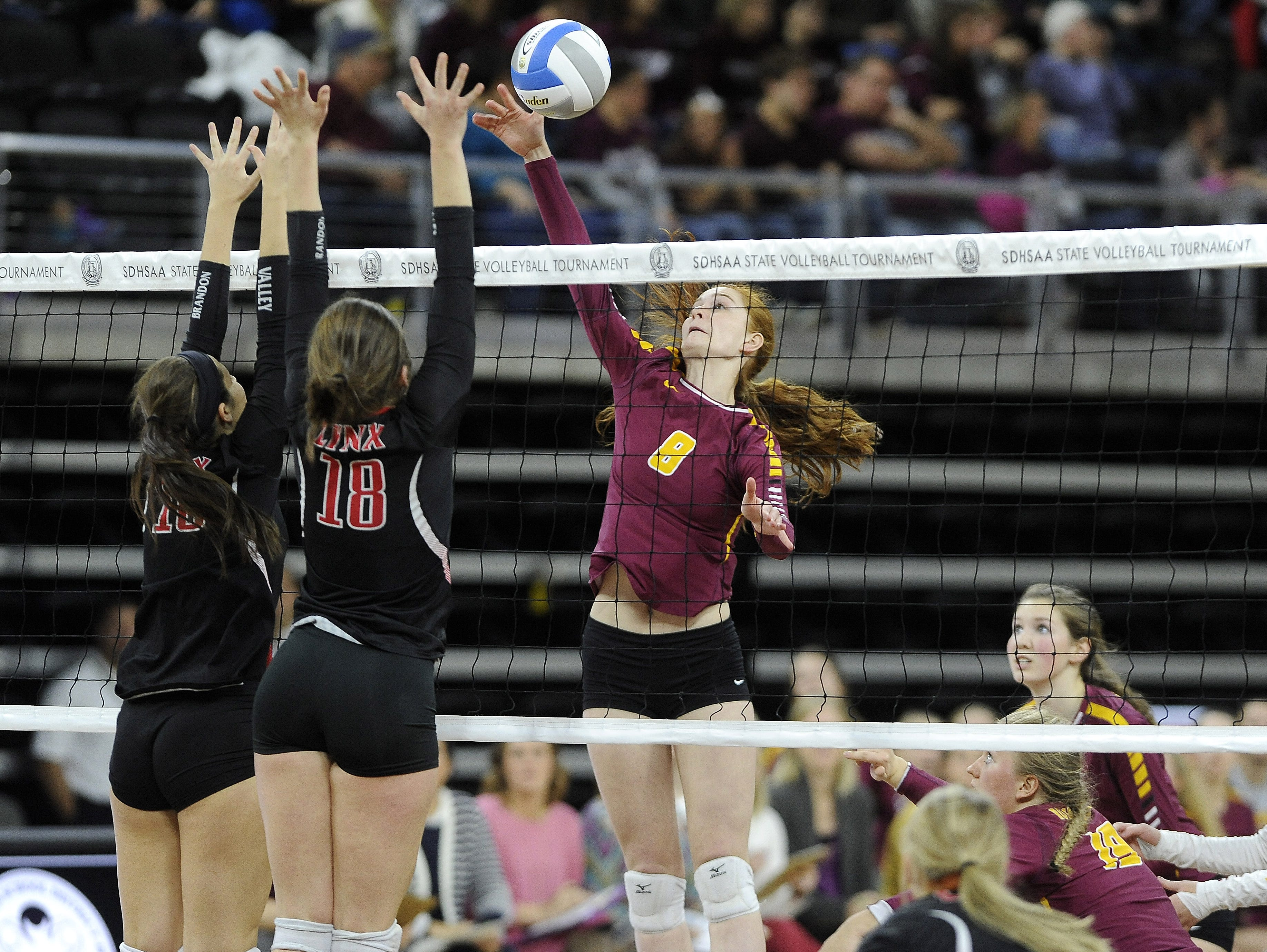 Roosevelt's #8 Mikaela Ahrendt sets the volleyball against Brandon Valley's #16 Abby Myers and #18 Elsie Zajicek during state volleyball action at the Denny Sanford Premier Center in Sioux Falls, S.D., Thursday, Nov. 19, 2015.