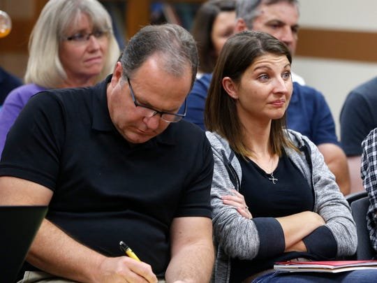 Angela Fulton, right, reacts as she listens to some of the arguments being made in support of the guidelines by school board members as the Rev. Len Maselli takes notes Monday, Aug. 15, 2016, during a school board meeting in Fairfield, Iowa.