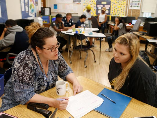 Science teacher Rebecca Wildman-Swartz works with student Alivia Peer on her earth science work Wednesday, May 17, 2017, as students behind them work with the math teacher on their work inside the Flex Academy classroom at Roosevelt High School in Des Moines. Peer is now a senior at the school.