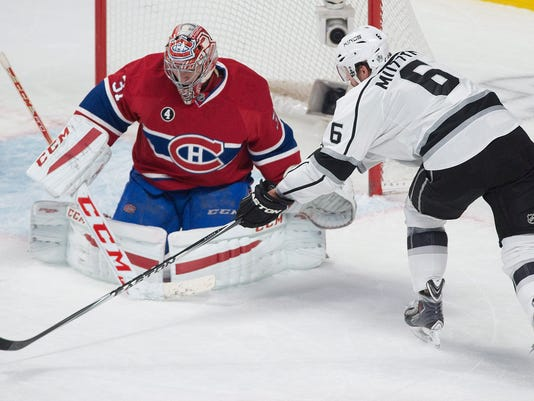 Los Angeles Kings' Jake Muzzin moves in on Montreal Canadiens goaltender Carey Price during the first period of an NHL hockey game, Friday, Dec. 12, 2014 in Montreal. (AP Photo/Canadian Press, Graham Hughes)