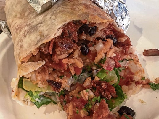 Pork burrito with contents spilling out onto plate Pork burrito with contents spilling out onto plate