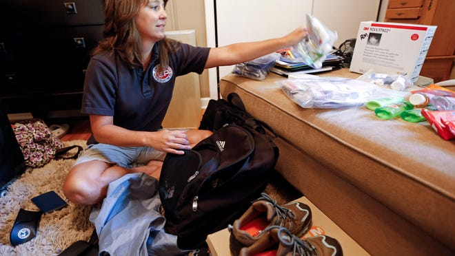Rendi Murphree, an epidemiologist with the Centers for Disease Control and Prevention who will soon be leaving for Monrovia, Liberia, packs for her trip at her home in Nashville, Tenn., Friday, Sept. 5, 2014. Murphree will be working at the airport in Monrovia, screening outbound passengers for the Ebola virus.