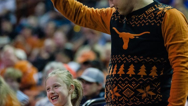 Texas fans Jeff Kyrish and Avery Kyrish, 8, cheer during a men's basketball game vs. Alabama-Birmingham in December. Learfield IMG College's Collegiate Licensing Co. partners with UT to manage the brand, including the logo.