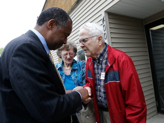Republican Dr. Ben Carson says a prayer with a supporter