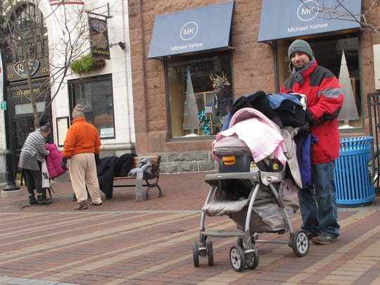 Wearing a new, donated winter jacket, Paul Pruessen, 36, of Milton, stands with his infant daughter, Angelena outside Sweetwaters American Bistro in downtown Burlington. Sweetwaters organized the coat and jacket giveaway with the Best Western Plus Windjammer Inn & Conference Center in South Burlington.