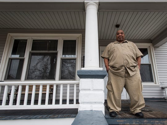 Shelter manager Bernard Evans stands on the front porch