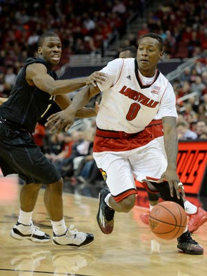 Feb 11, 2015; Louisville, KY, USA; Louisville Cardinals guard Terry Rozier (0) dribbles against Pittsburgh Panthers guard Josh Newkirk (13) during the first half at KFC Yum! Center. Mandatory Credit: Jamie Rhodes-USA TODAY Sports