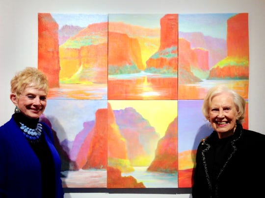 Carol Marshall (left) and Lucille Schmitt stand by their favorite paintings of the Grand Canyon painted en plein aire by Leslie Masters.