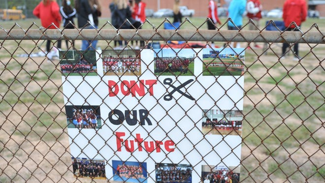 Approximately 75 students and parents gathered outside the Coventry Public Schools office Friday to protest budget cuts that might take away all afterschool activities, including sports. A sign posted on the fence conveyed their message.