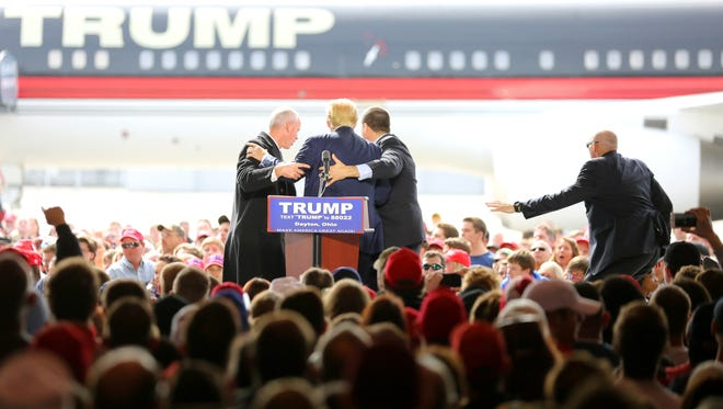 Sat., March 12, 2016: Secret service agents run to Donald Trump as a man rushes the stage at a rally at a Dayton airport hangar. The Enquirer/Carrie Cochran