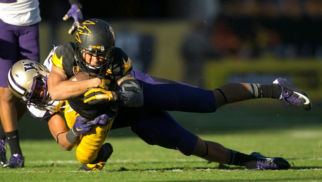 ASU 's D.J. Foster is tackled by Washington's Brian Clay during the fourth quarter of the college football game at Sun Devil Stadium in Tempe on Saturday, November 14, 2015.