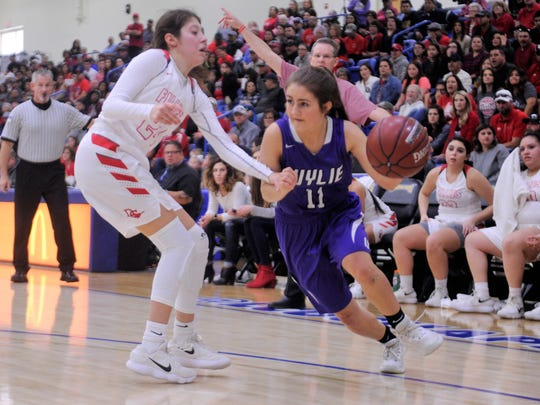 Wylie guard Madi Latham (11) dribbles around Denver City's Arielle Adams (24) during the Lady Bulldogs' 44-41 loss in the Region I-4A championship game at the Lubbock Christian University Rip Griffin Center on Saturday, Feb. 24, 2018.