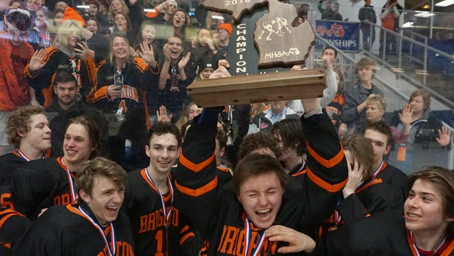 Brighton's Jake Demski holds the championship trophy after the Bulldogs beat Saginaw Heritage, 5-2, in the state Division 1 title game on Saturday, March 10, 2018 at USA Hockey Arena in Plymouth.