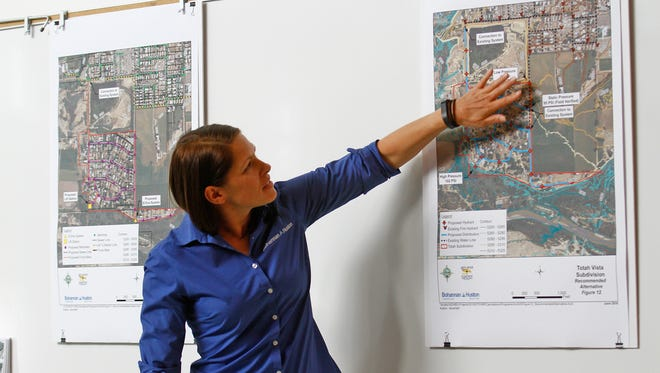 Kirsty Bramlett, an engineer with Bohannan Huston, talks about plans for linking houses in the Totah subdivision to the Farmington water and sewer systems during a meeting on Thursday at the Sycamore Park Community Center in Farmington.