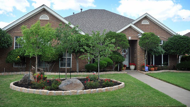 This home on Wind Song Drive features a landscape  professionally maintained by a lawn care company but many homeowners can achieve similar results with a little research and advice from their local nursery.