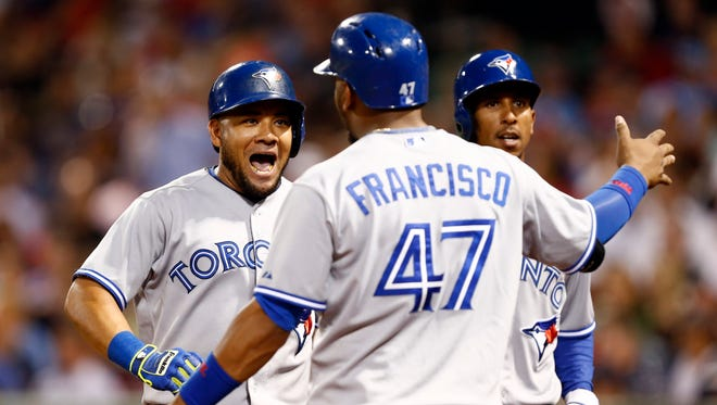 Toronto Blue Jays left fielder Melky Cabrera (left) celebrates his home run against the Boston Red Sox with third baseman Juan Francisco (47) and center fielder Anthony Gose (right) during the sixth inning at Fenway Park.