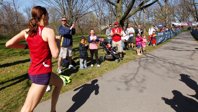 A crowd at the finish line cheers on Sarah Loerch, of Rochester, as she heads to the finish line of the Pink Ribbon Run & Walk in 2014.