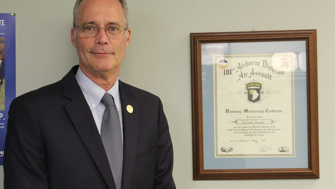 Bill Harpel, Clarksville's military liaison, stands next to his certificate in his office designating him an honorary member of the 101st Airborne Division.