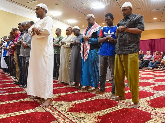 Muslim men do their evening prayers watched by non-Muslim community members at the back of the worship space Thursday, June 23 at the Islamic Center in St. Cloud.