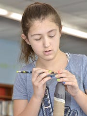 Sandshore Elementary School fifth-grader Isabella Pepe works on the nose cone of a rocket.