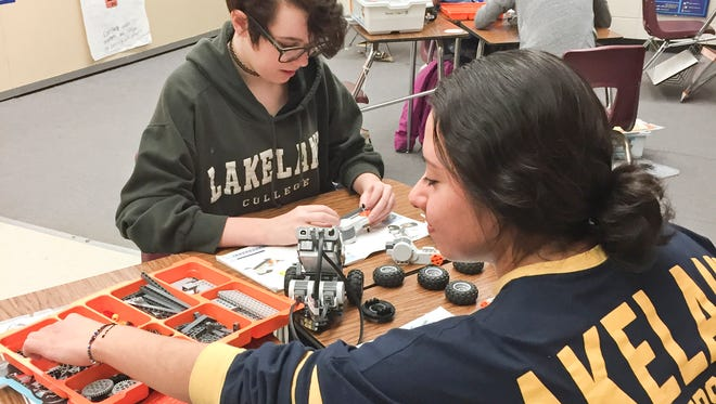 Students in the Plymouth High School STEM Girls Rock club build small model car out of various household materials. The club pairs middle and high school students with Lakeland University science and math students.