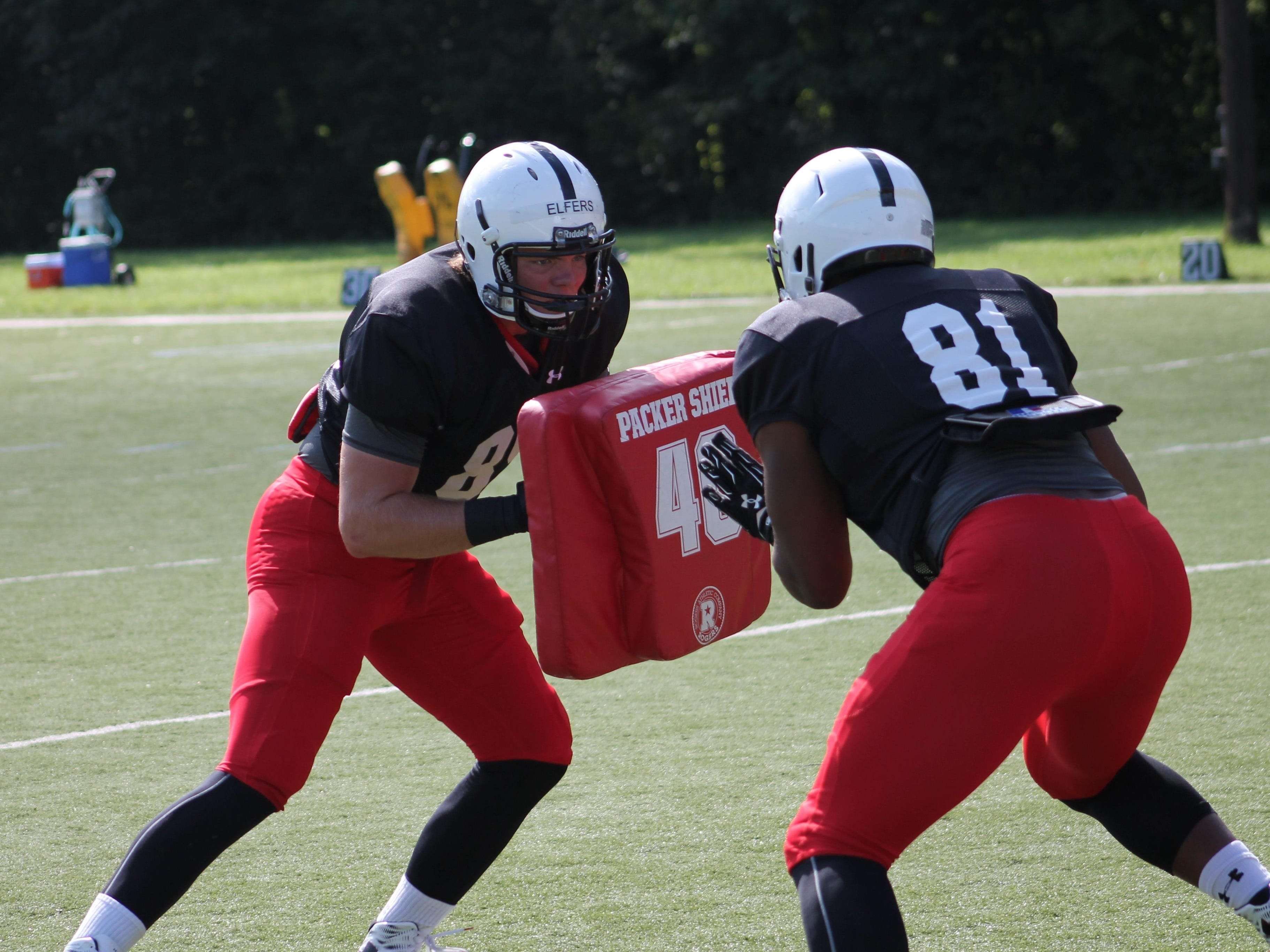 Redshirt freshman Jake Elfers works on a blocking drill with UC starting tight end D.J. Dowdy (No. 81).