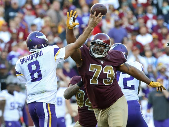 Minnesota Vikings quarterback Sam Bradford (8) throws the ball as Washington Redskins defensive lineman Cullen Jenkins (73) chases in the fourth quarter at FedEx Field.