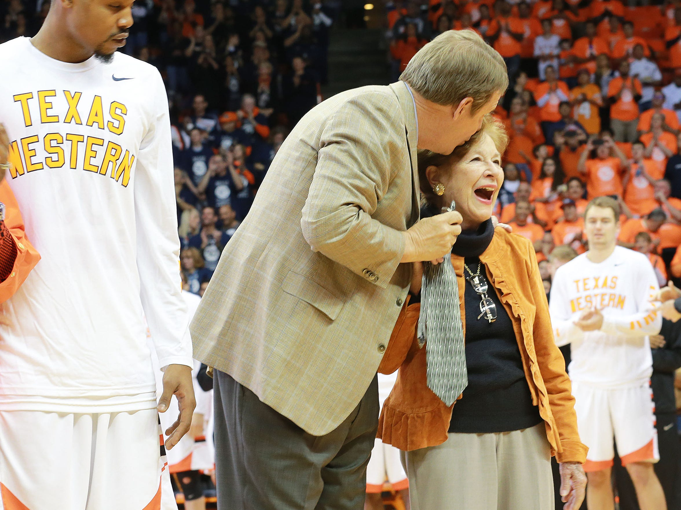 UTEP head basketball coach Tim Floyd kisses Mary Haskins, widow of Naismith Memorial Basketball Hall of Fame coach Don Haskins, during a pregame ceremony Saturday at the Don Haskins Center. Members of the 1966 NCAA Championship team were honored Saturday. Floyd is holding a clip-on tie like the one coach Haskins used to wear.