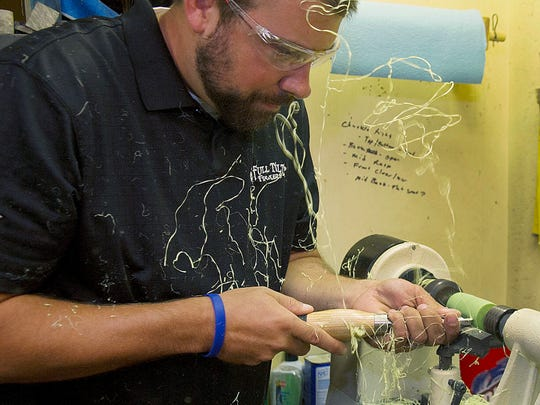 Brandon Brown uses a lathe to make the barrel of his hand-turned duck call in his shop in Wapello.