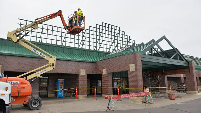 A crew from general contractor Carlson-LaVine, Roseville, moves into position to remove the gridwork Tuesday morning over the top of the Byerly's grocery store on 25th Avenue in St. Cloud. The entrance is undergoing a renovation that will incorporate a sign with the new Lunds & Byerlys name.