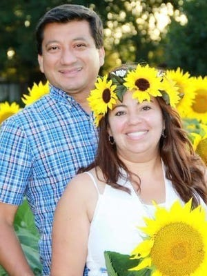 Polo and Silvia Delacruz, pastors at El Encuentro, smile for a photo in a sunflower field. Silvia Delacruz died July 23 after testing positive for the coronavirus a month earlier.