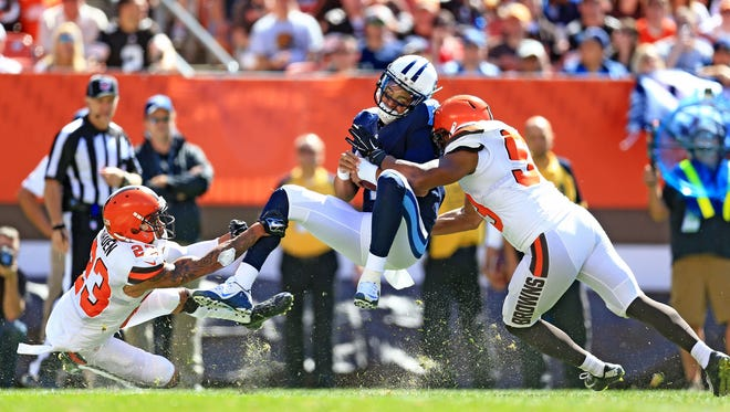 Sep 20, 2015; Cleveland, OH, USA; Tennessee Titans quarterback Marcus Mariota (8) is tackled by Cleveland Browns cornerback Joe Haden (23) and inside linebacker Craig Robertson (53) during the first quarter at FirstEnergy Stadium. Mandatory Credit: Andrew Weber-USA TODAY Sports