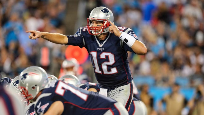 New England Patriots quarterback Tom Brady (12) calls out the signal change during the second quarter at Bank of America Stadium.
