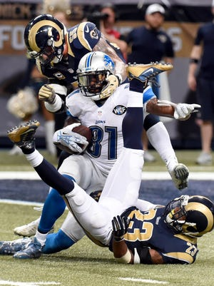 Lions wide receiver Calvin Johnson (81) is stopped by Rams linebacker James Laurinaitis, top, and free safety Rodney McLeod after catching 16-yard pass during the fourth quarter Sunday in St. Louis.