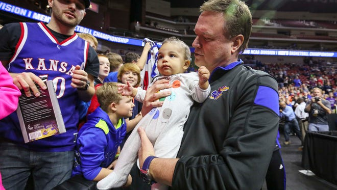 Kansas head coach Bill Self holds 7 month old Jackson Kayembe of Waukee following their open practice Wednesday March 16, 2016, at Wells Fargo Arena, In Des Moines, Iowa. Kansas will play Austin Peay Thursday in their NCAA men's basketball tournament first round game.