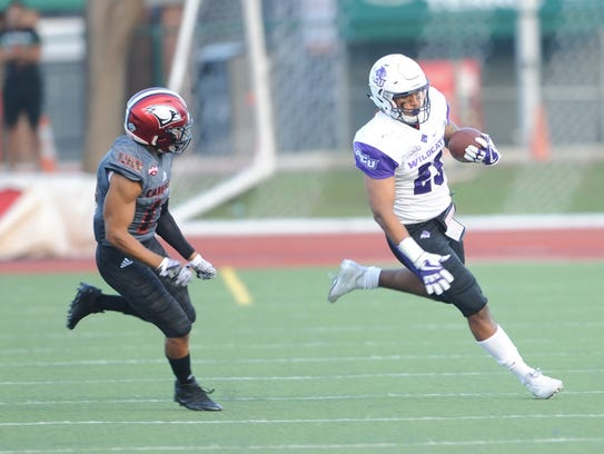 ACU running back Tracy James, right, evades a Incarnate