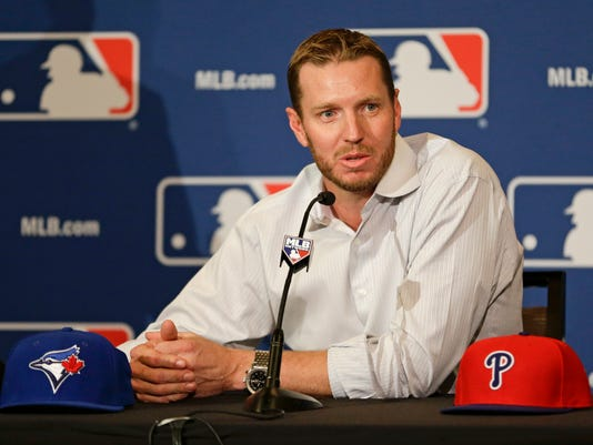 FILE - In this Dec. 9, 2013, file photo, two-time Cy Young Award winner Roy Halladay answers questions after announcing his retirement after 16 seasons in the major leagues with Toronto and Philadelphia, at the MLB winter meetings in Lake Buena Vista, Fla. An autopsy report says Halladay had evidence of amphetamine, morphine and an insomnia drug in his system when he died in a small plane crash in Florida last year.( AP Photo/John Raoux, File)