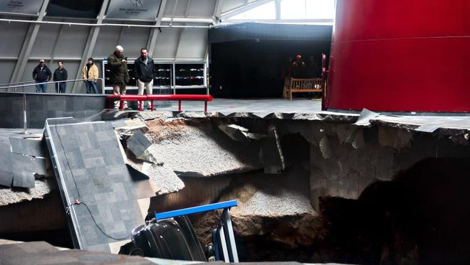 Officials on Feb. 12, 2014, view a sinkhole that opened up in the Skydome showroom at the National Corvette Museum in Bowling Green, Ky. Eight display cars were swallowed by the hole.