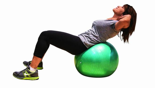 Elizabeth Frano, a personal trainer at Pure Fit Club in White Plains, demonstrates how to do an abdominal crunch on an exercise ball.