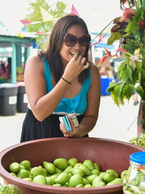 Jolynh Brubaker samples a piece of mango from Lou's Mangoes stand during the 10th Annual Agat Mango Festival in Agat on May 7, 2016.