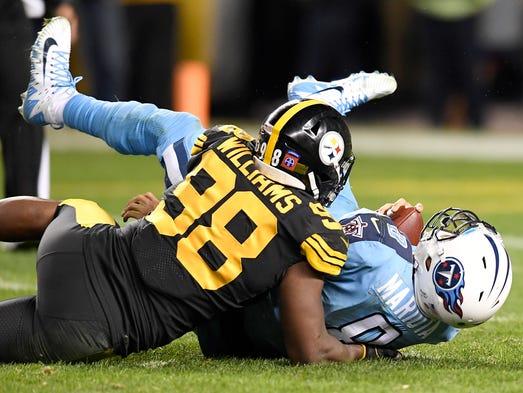 Titans quarterback Marcus Mariota (8) is sacked by