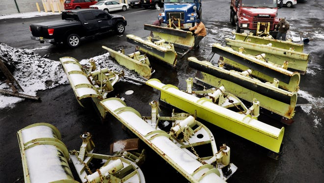 Workers attach snow plows to trucks at a New Jersey Dept. of Transportation maintenance yard, Monday, Jan. 26, 2015, in Newark, N.J. New Jersey Gov. Chris Christie declared a state of emergency saying NJ Transit will shut down late Monday as a winter storm threatens to dump as much as two feet of snow over parts of the state. (AP Photo/Mel Evans)