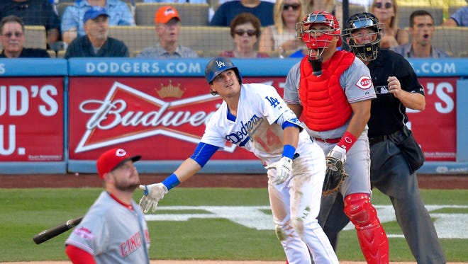 Los Angeles Dodgers' Kike Hernandez, second from left, drops his bat as he hits a three-run home run as Cincinnati Reds starting pitcher David Holmberg, left, and catcher Brayan Pena, second from right, watch along with home plate umpire Dana DeMuth during the second inning of a baseball game, Saturday, Aug. 15, 2015, in Los Angeles.