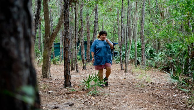 """Virginia """"Shorty"""" Dubberly walks through a wooded area on the 2800 block of Southeast Market Place after leaving her camp to run errands Jan. 4, 2017, in Stuart. Dubberly, originally of Fort Pierce, has been homeless less than a year."""
