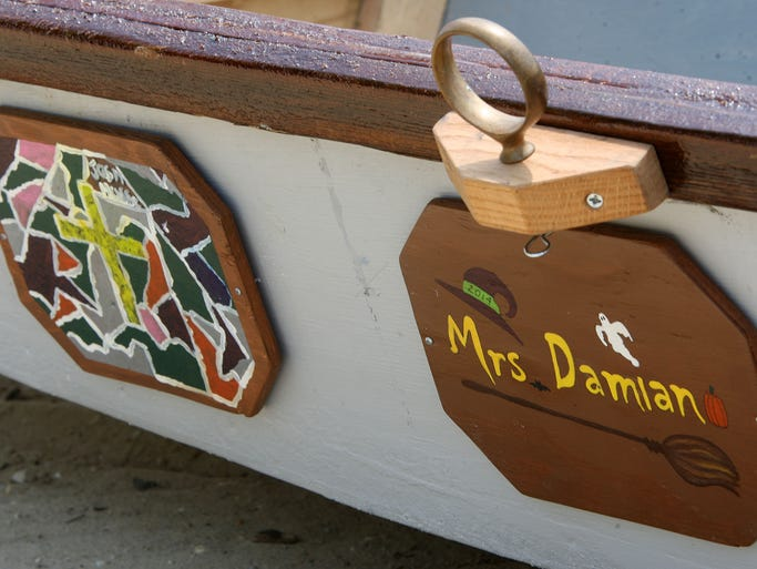 """Students from Cumberland Regional High School, as well as Bridgeton's Broad St. School, put personalized plaques on the side of the boats that they made as part of the """"Float Your Boat"""" project, Tuesday, Jun. 17, 2014 in Pittsgrove.  Staff Photo/Sean M. Fitzgerald"""